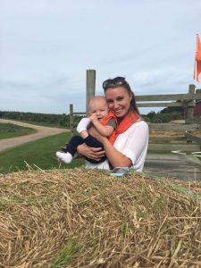 Mom and son in front of a hay bale